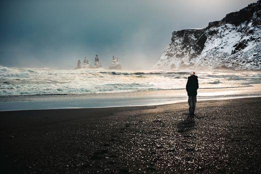 Traveler, woman standing on the black volcanic beach and enjoying amazing view on basalt sea stacks, Reynisdrangar in Atlantic ocean near Vik Myrdal, Iceland