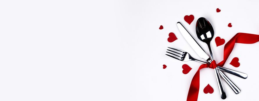 Cutlery set tied with silk ribbon and hearts isolated on white background Valentine day romantic dinner concept