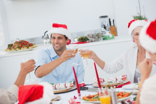 Happy family clinking their glasses of white wine for christmas
