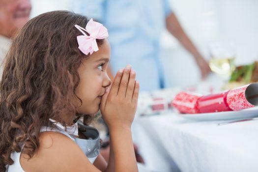 Little girl sitting praying at table for christmas dinner