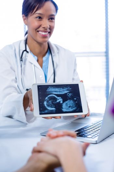 Doctor showing babies ultrasound scan on digital tablet in hospital
