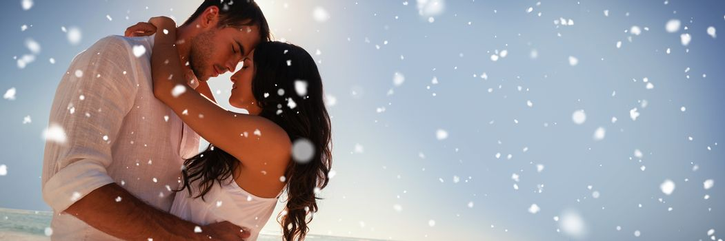 Romantic couple embracing  against snow falling