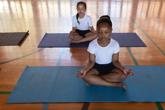Front view of schoolgirls doing yoga and meditating on a yoga mat in school