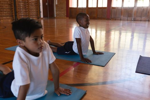 Side view of schoolkids doing yoga position on a yoga mat in school gymnasium