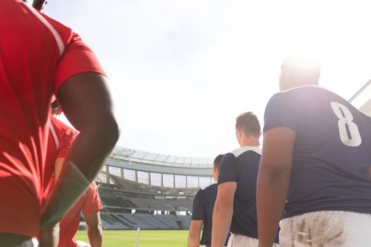 Low angle view of diverse male rugby players standing in a row at stadium while mentally preparing for match on a sunny day.