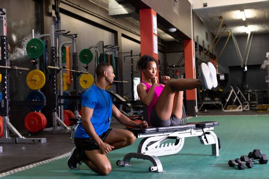 Side view of an African-American woman doing curl ups on a bench and an African-American man assisting her inside a room at a sports center. Bright modern gym with fit healthy people working out and training. Bright modern gym with fit healthy people working out and training