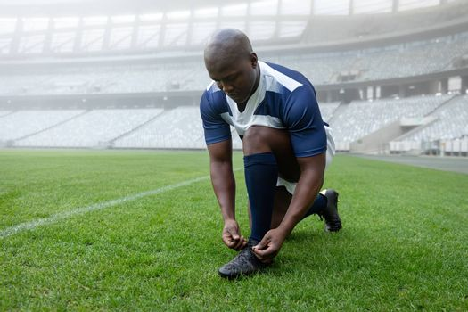 Front view of African american male rugby player tying shoelaces in the stadium
