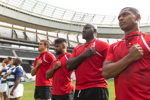 Front view of proud diverse rugby team taking pledge together in stadium