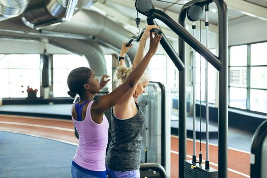 Side view of young pretty African-american female trainer assisting active senior Caucasian  woman on lat pulldown machine in fitness studio. Bright modern gym with fit healthy people working out and training