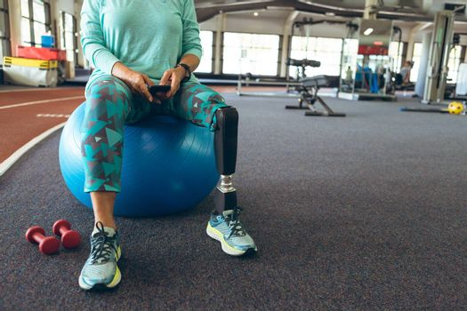 Low section of disabled active senior Caucasian woman with leg amputee using mobile phone while sitting on exercise ball in fitness center. Strong active senior female amputee training and working out