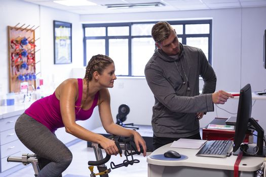 Front view of young Caucasian male trainer and pretty Caucasian female athletic discussing over computer in fitness center. Bright modern gym with fit healthy people working out and training