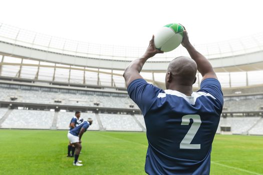 Rear view of African American male rugby player throwing rugby ball in stadium. With players in the background.