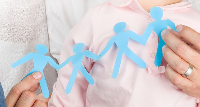 Man's hands holding a blue paper cut group of people, conceptual photo of standing together, teamwork, friendship, and family support