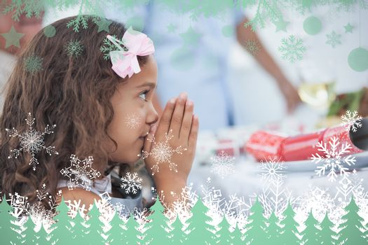 Little girl sitting praying at table against snowflakes and fir trees in green