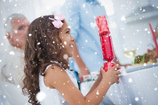 Composite image of Cute little girl holding crackers against snow falling