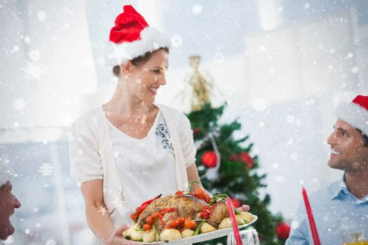 Cheerful woman wearing santa hat and bringing a roast chicken against snow