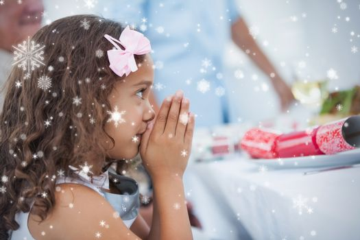 Composite image of Little girl sitting praying at table against snow falling