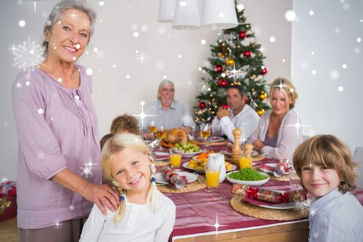 Composite image of Grandmother and granddaughter standing beside the dinner table against snow falling