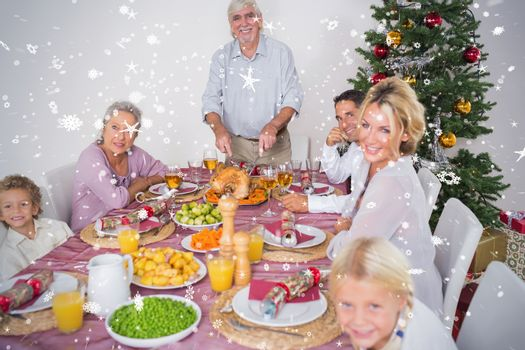 Composite image of Happy family at christmas dinner against snow falling