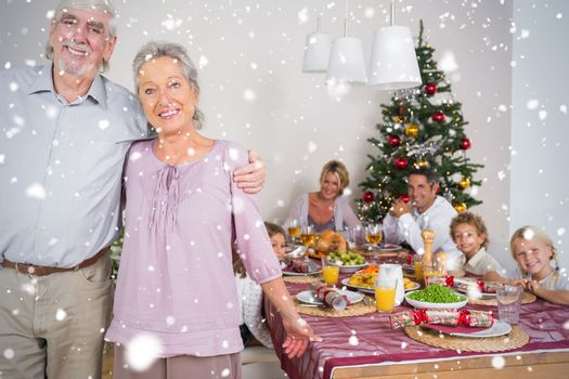 Composite image of Grandparents standing by the dinner table against snow falling