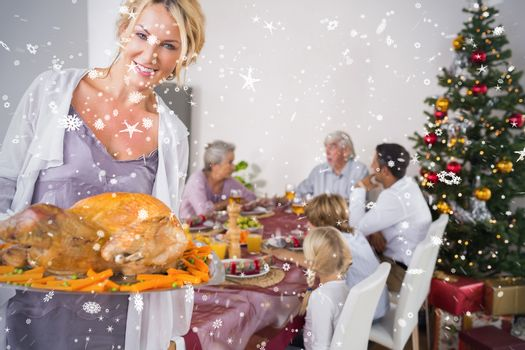 Composite image of Proud mother showing roast turkey against snow falling