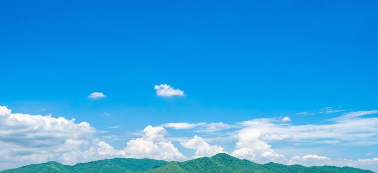 Blue sky and white cumulus clouds over green mountain. Beauty in nature. White fluffy clouds. Tropical nature. Sunny day. Heaven and tranquil scene. Summer weather. Love nature concept. Fresh air.