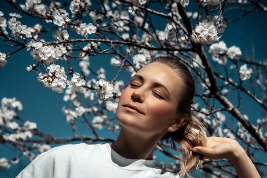 Fashion portrait of a nice female with closed eyes of pleasure enjoying beauty and freshness of spring nature, spending time in blooming garden, weekend in countryside