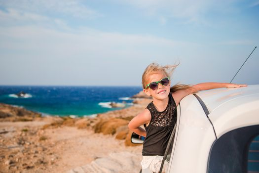 Little girl on vacation travel by car. Summer holiday and car travel concept