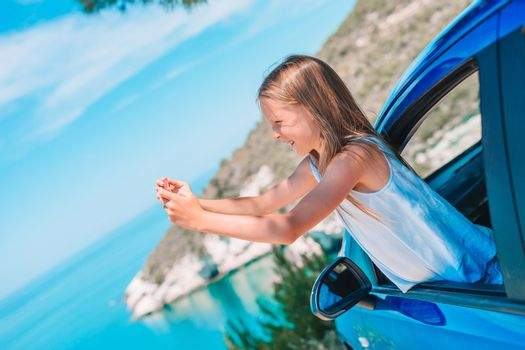 Little girl traveling by car and making photo of beautiful landscape. Summer holiday and car travel concept