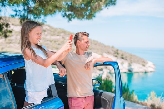 Little girl with father traveling by car and making photo of beautiful landscape. Summer holiday and car travel concept