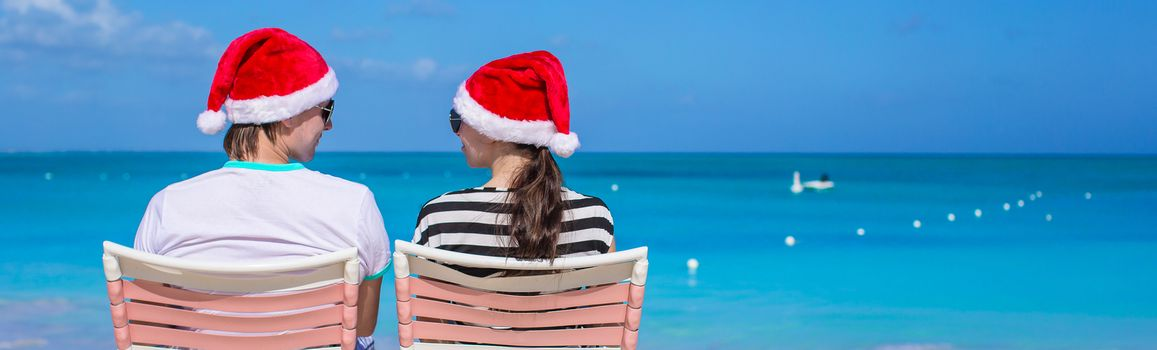 Young romantic couple in red Santa hats sitting on tropical white sand beach