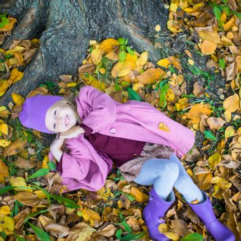 Little happy girl in autumn park on sunny day