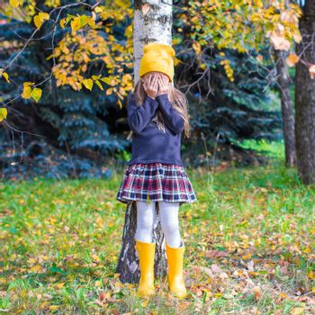 Little girl playing hide and seek near the tree in autumn forest