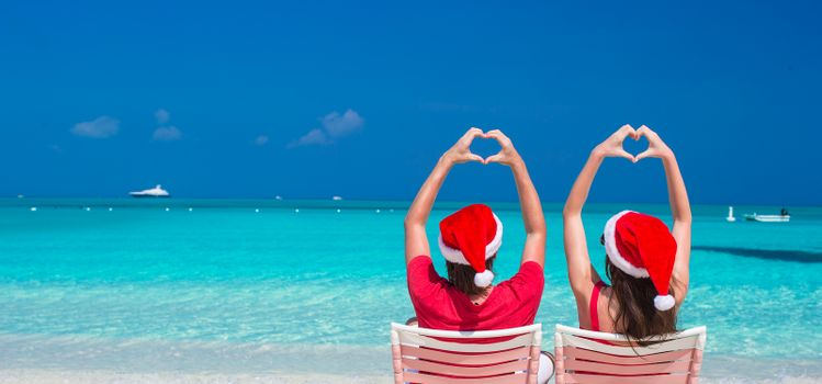 Happy romantic couple in red Santa hats at tropical beach relaxing on sunbeds