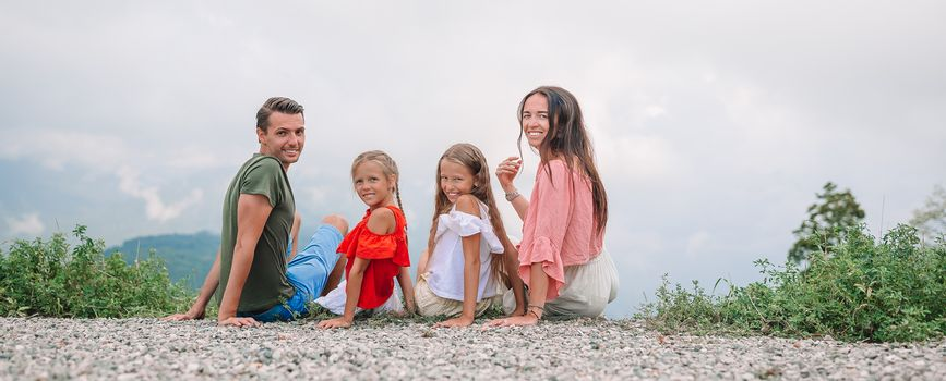 Beautiful family of four in mountains on summer vacation. Family vacation