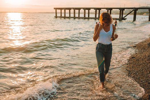 Fashion portrait of stylish girl on the beach at sunset