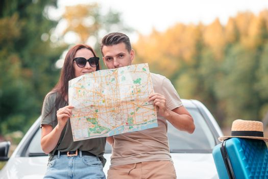 Young family with map while travel by car