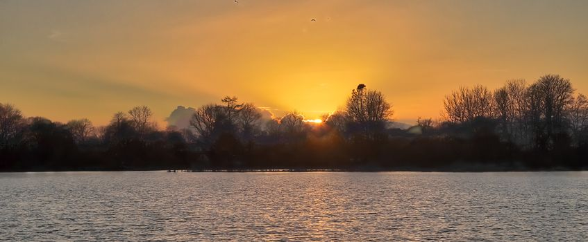 Beautiful and romantic sunset at a lake in stunning yellow and orange colors