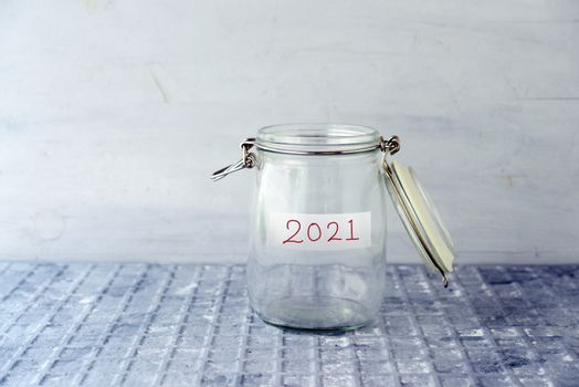 Coins in glass money jar with 2021 label, financial concept.
