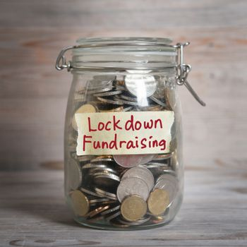 Coins in glass money jar with lockdown fundraising label. Vintage wooden background with dramatic light.