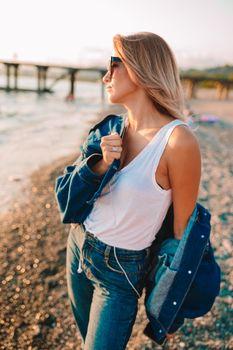 Fashion portrait of stylish woman on the beach at sunset