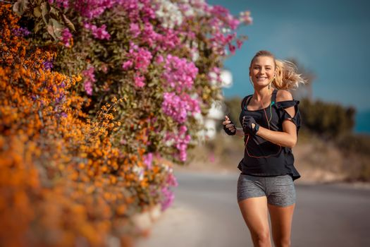 Sportive Woman on the Workout among Beautiful Blooming Flowers. Active Female Running Outdoors and Listening Music. Weight Loss. Happy Healthy Lifestyle.