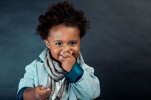Portrait of a Nice Little African-American Boy Dressed in Stylish Clothes Posing over Dark Background in the Studio. Baby Model.