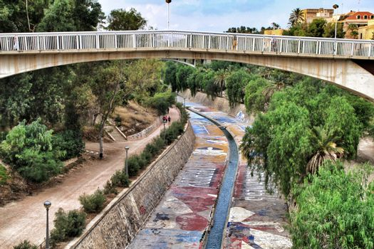 Elche, Alicante, Spain- September 12, 2018: Beautiful and Lush landscape of the Vinalopo riverbed in Elche, Alicante. People walking between vegetation.