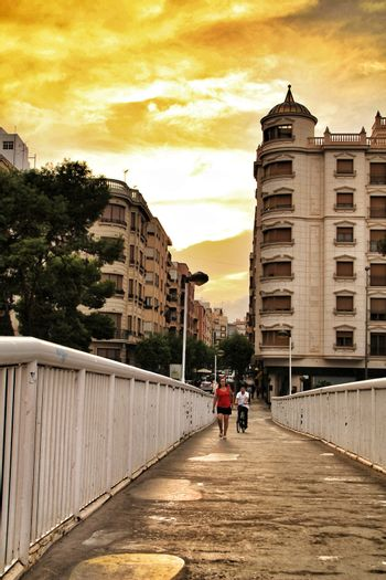 Elche, Alicante, Spain- September 12, 2018: People crossing a bridge at sunset in Elche. Beautiful buildings in the background.