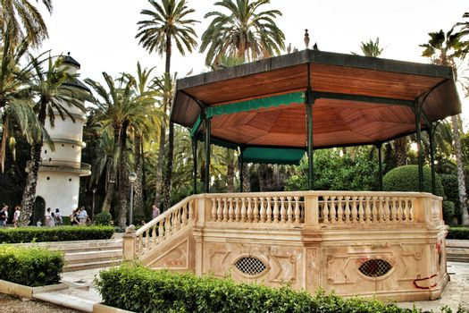 Elche, Alicante, Spain- September 16, 2018: Beautiful and vintage music kiosk in the municipal park of Elche between palm trees. Elche, Alicante, Spain.