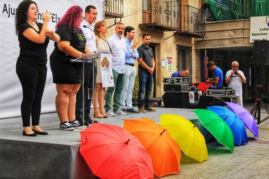 Elche, Spain- June 28, 2018:Rainbow flag of umbrellas in the town hall read the manifest in the Gay Pride Day in Elche, Alicante, Spain.