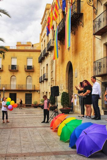 Elche, Spain- June 28, 2018:Rainbow flag hanging from the balcony of the town hall and colorful balloons while politicians reading the manifest in the Gay Pride Day in Elche, Alicante, Spain.