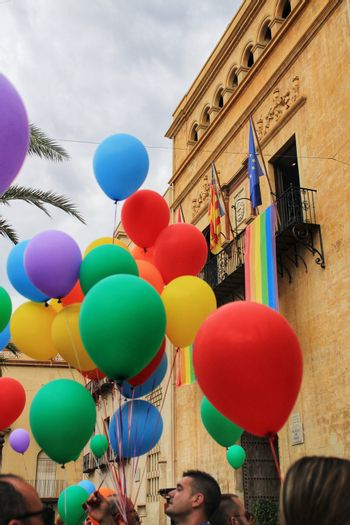 Rainbow flag hanging from the balcony of the town hall and colorful balloons while politicians reading the manifest in the Gay Pride Day in Elche, Alicante, Spain.