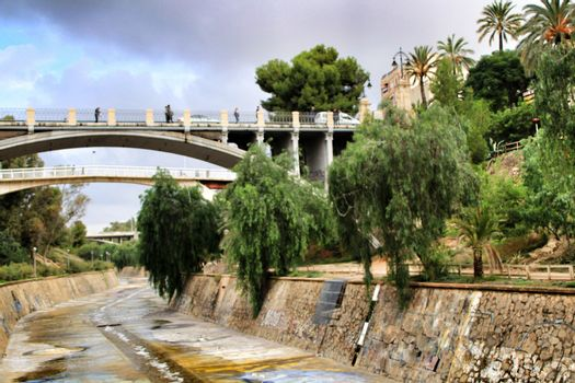 Elche, Alicante, Spain- November 16, 2018 - Landscape of the hillside of the Vinalopo River in Elche with its bridges and green vegetation after a rainy day of Autumn